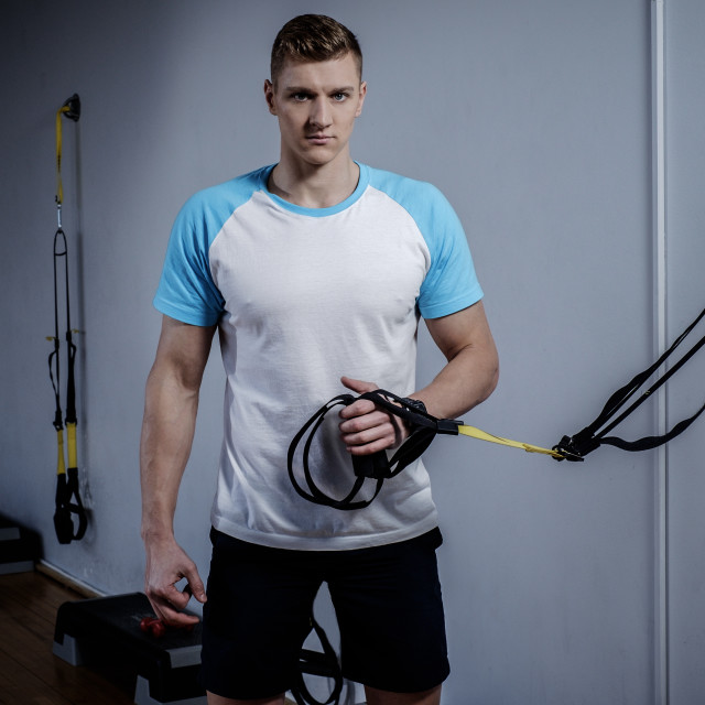 """Attractive man during workout with suspension straps In The Gym's Studio"" stock image"