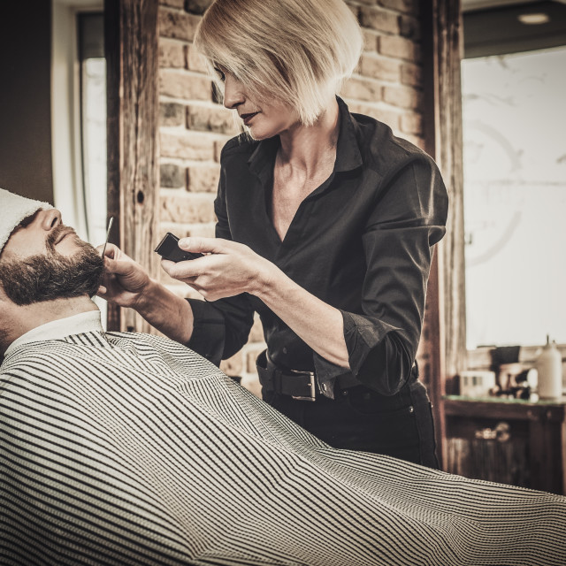 """Client during beard and moustache grooming in barber shop"" stock image"