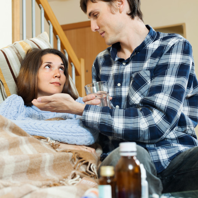 """Guy giving medicament to unwell wife"" stock image"