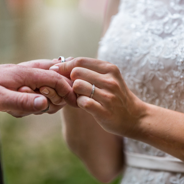 """""""Exchanging rings during a wedding ceremony, focusing on the engagement ring"""" stock image"""
