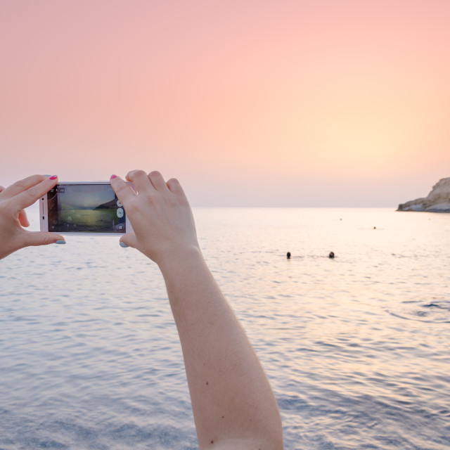 """View Landscape Sunset on a woman's mobile smart phone"" stock image"