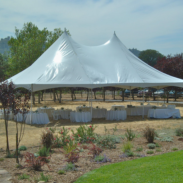"""""""A large tent is set up to hold a wedding reception outdoors in a field in..."""" stock image"""