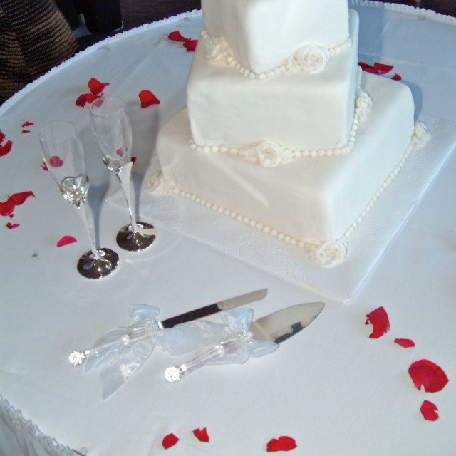 """""""A white 3 tier square wedding cake with icing decorations is displayed on a..."""" stock image"""