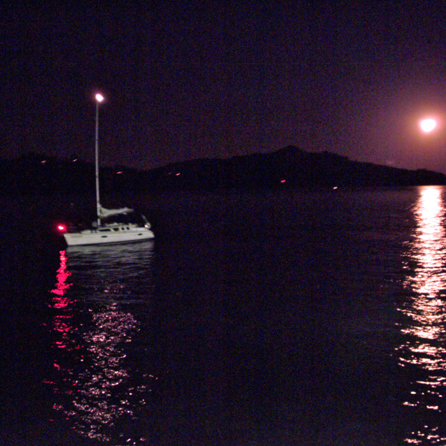 """""""Grainy photograph of a boat lit by moonlight on San Francisco Bay at night"""" stock image"""