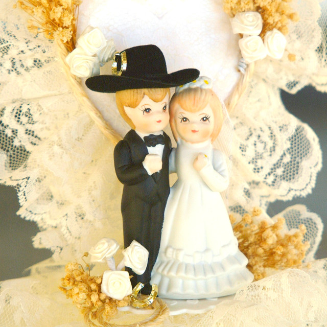 """""""A bride and groom cowboy wedding cake topper is on top of a white wedding cake."""" stock image"""