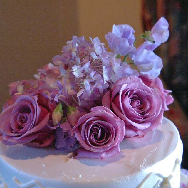 """""""The top of a white multi tier wedding cake with pink and purple flowers."""" stock image"""