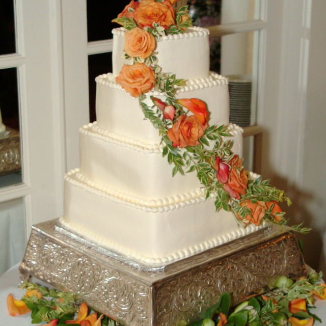 """""""A white 4 tier square wedding cake decorated with flowers is displayed on a..."""" stock image"""