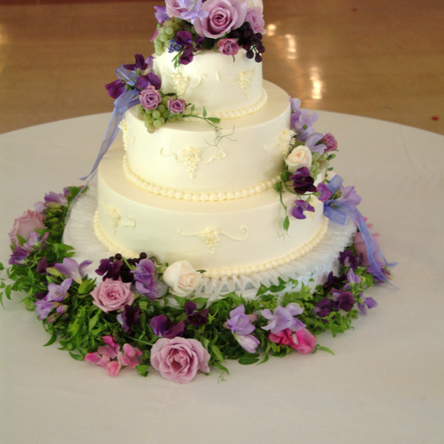 """""""A white 3 tier wedding cake with pink and purple live flowers is displayed on..."""" stock image"""