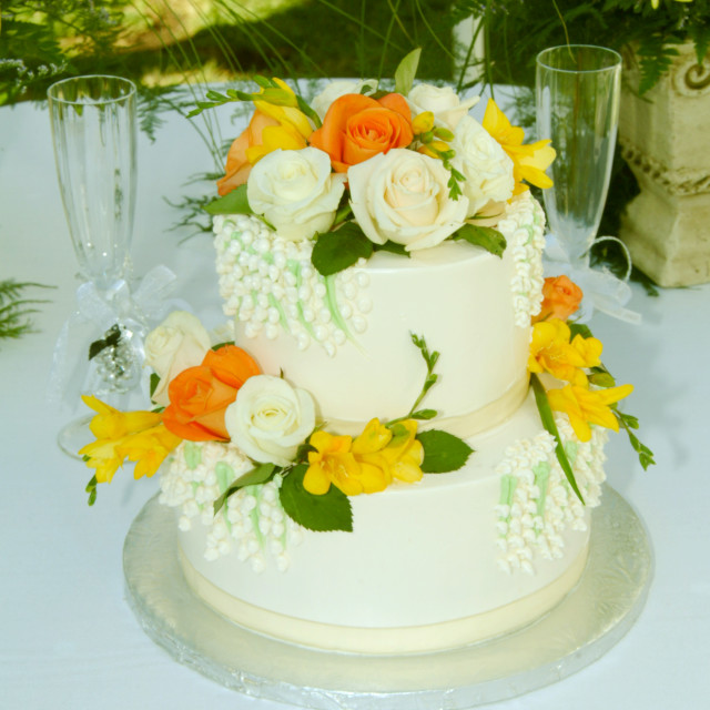 """""""A white 2 tier wedding cake with floral decorations is displayed on a table."""" stock image"""