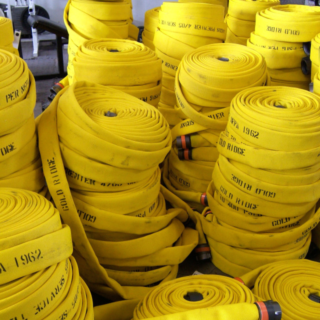 """""""A group of brand new yellow fire hoses are stacked ready for inspection"""" stock image"""