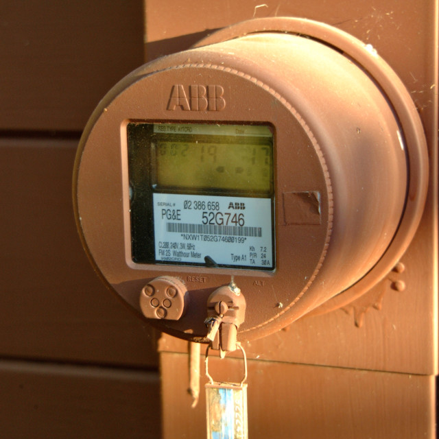 """""""A locked digital electric meter is mounted on an outdoor wall."""" stock image"""