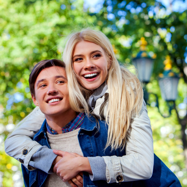 """""""Young couple hugging and flirting in park."""" stock image"""