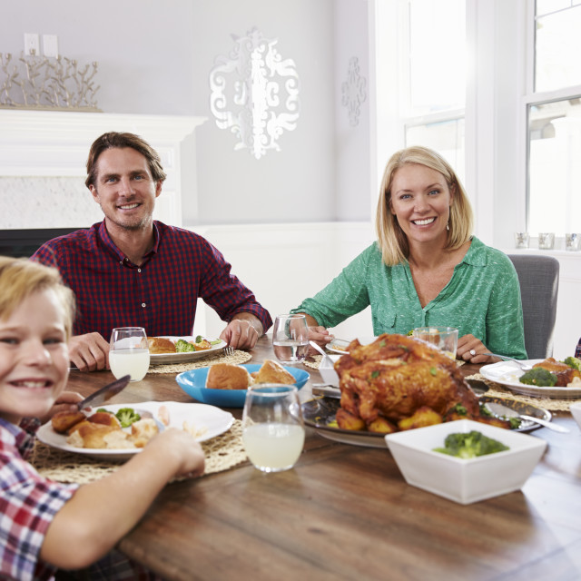 """Portrait Of Family Sitting Around Table Eating Meal At Home"" stock image"