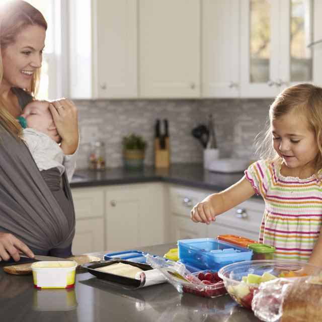 """Mum holding baby watches older daughter preparing food"" stock image"