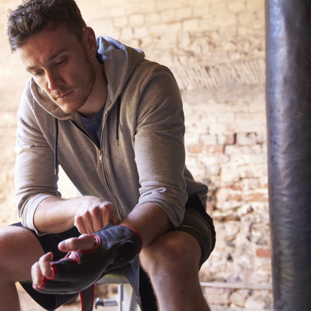 """""""Male Boxer Putting On Gloves In Gym"""" stock image"""