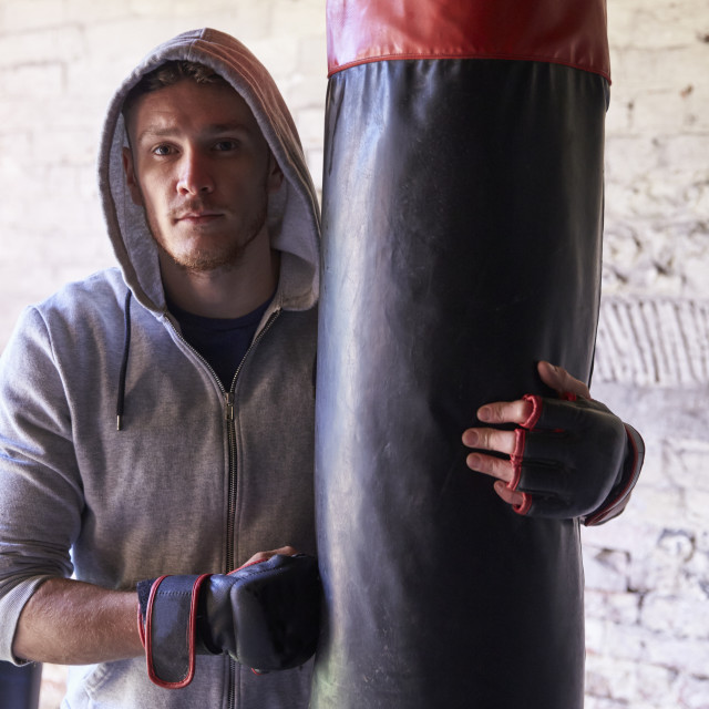 """""""Portrait Of Young Male Boxer With Punch Bag In Gym"""" stock image"""