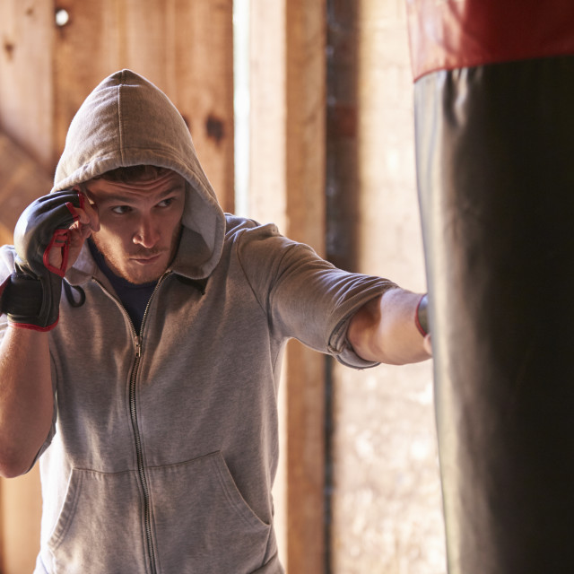 """Young Male Boxer Working Out With Punchbag In Gym"" stock image"