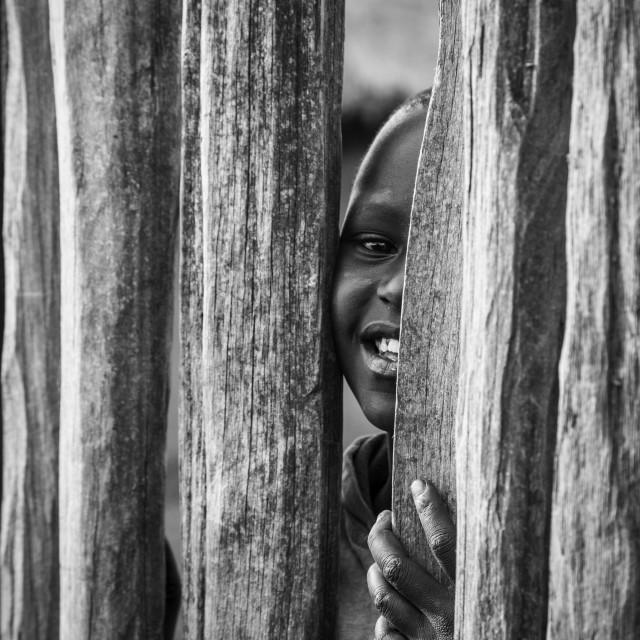 """Child peeks through a fence"" stock image"