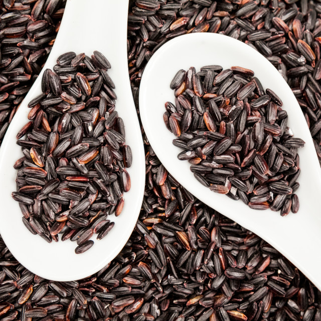 """Black rice in white spoons"" stock image"