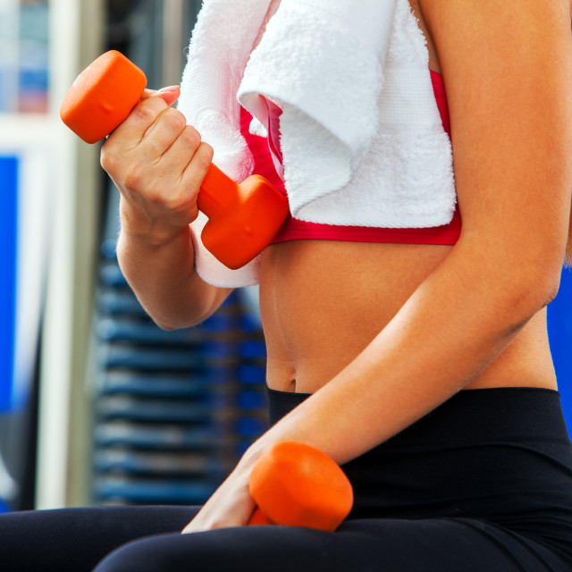 """""""Body part sport girl lift dumbbells in gym. Biceps foreground."""" stock image"""