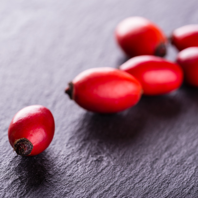 """Several red hips placed on black slate stone"" stock image"