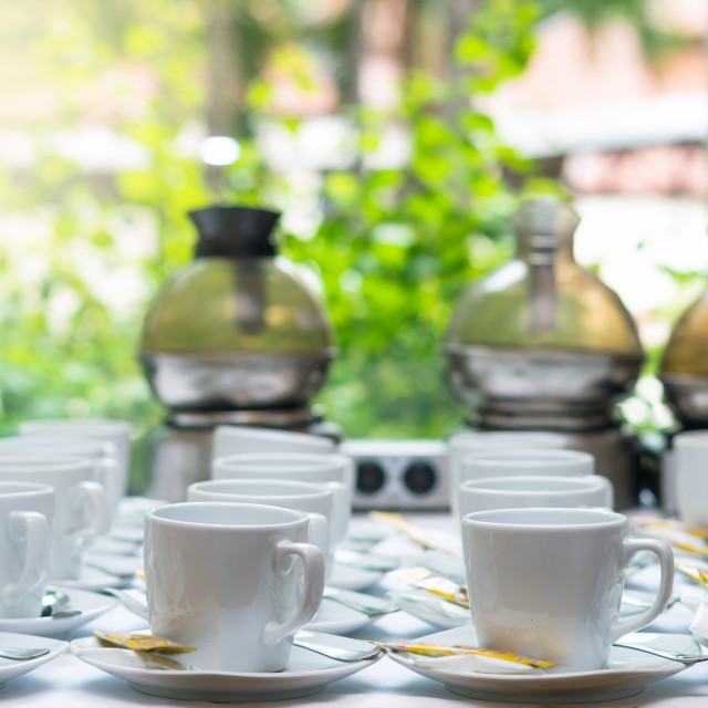 """""""Many rows of white coffee cup with saucer and teaspoon on table and coffee..."""" stock image"""