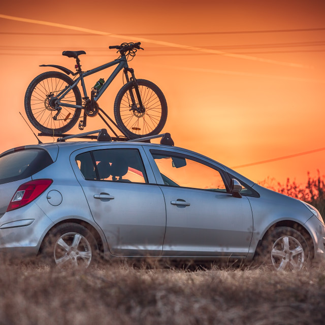 """Car is transporting bicycle on the roof"" stock image"