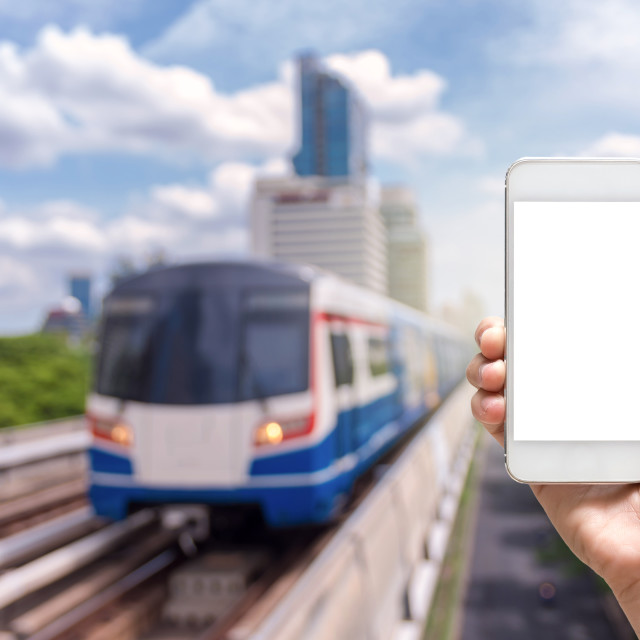 """""""Hand holding tablet taking photo on abstract Blurred photo of sky train with..."""" stock image"""