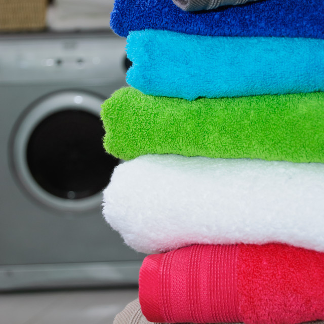 """Colorful stack of folded towels with washing machine in background"" stock image"