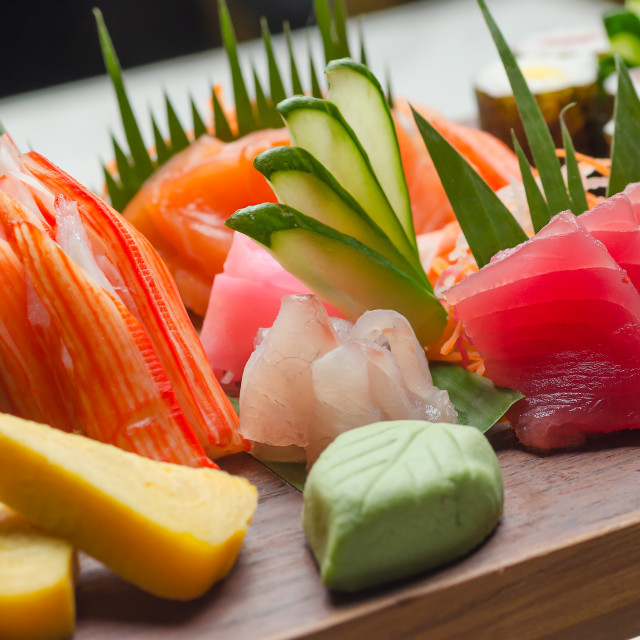 """A colorful platter of sashimi sushi with tuna and crab sticks in foreground and cucumber decorations"" stock image"