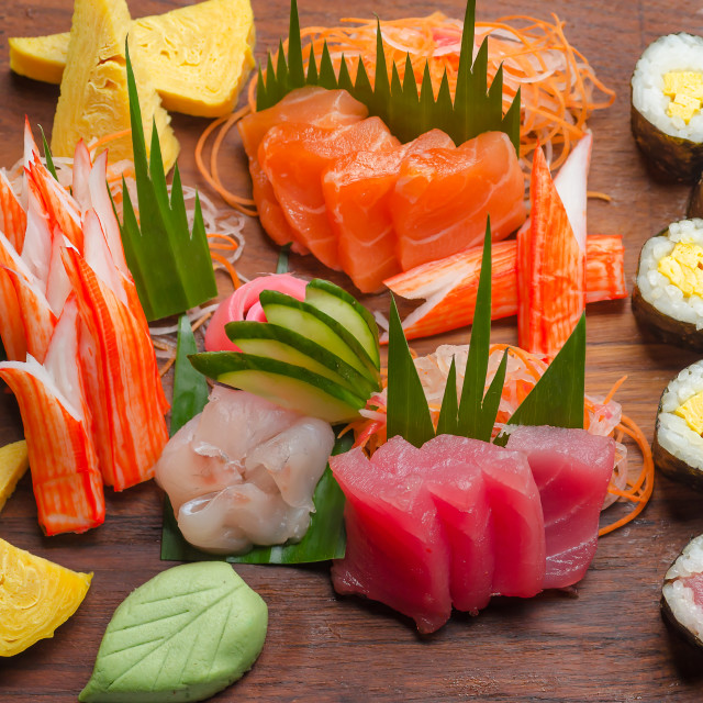 """Down top view of sushi platter with salmon, tuna, maki rolls, wasabi and crab sticks on wooden board with cucumber dressing"" stock image"