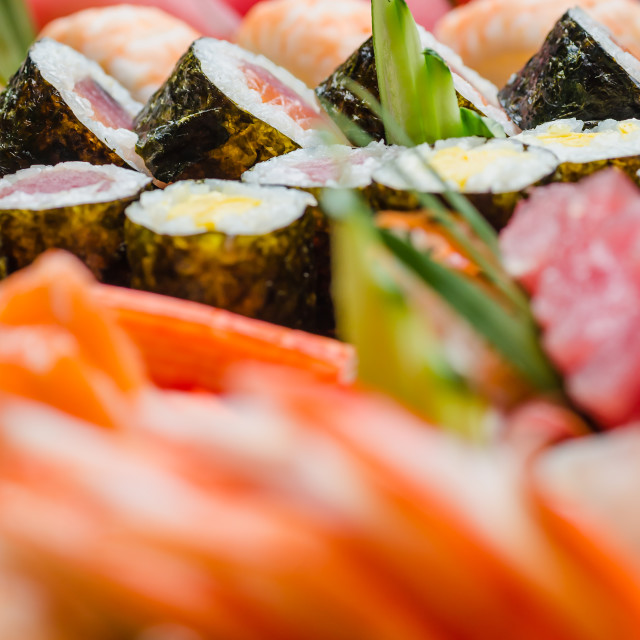 """Close up side view of maki sushi on a platter with blurred sushi in foreground and backgound"" stock image"
