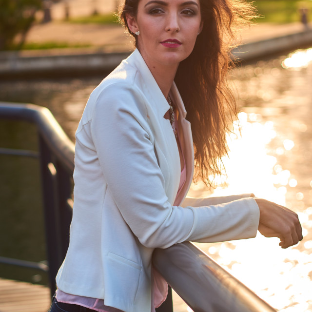 """Beautiful young woman outside city urban walking park gazing over canal sunset"" stock image"