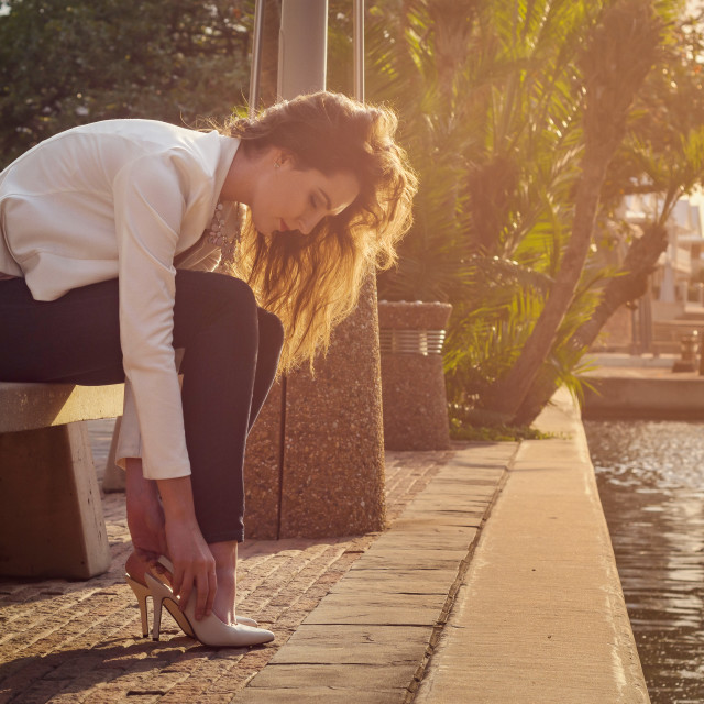 """Beautiful young woman in jeans and a jacket putting her shoes on sitting on a bench near a canal"" stock image"