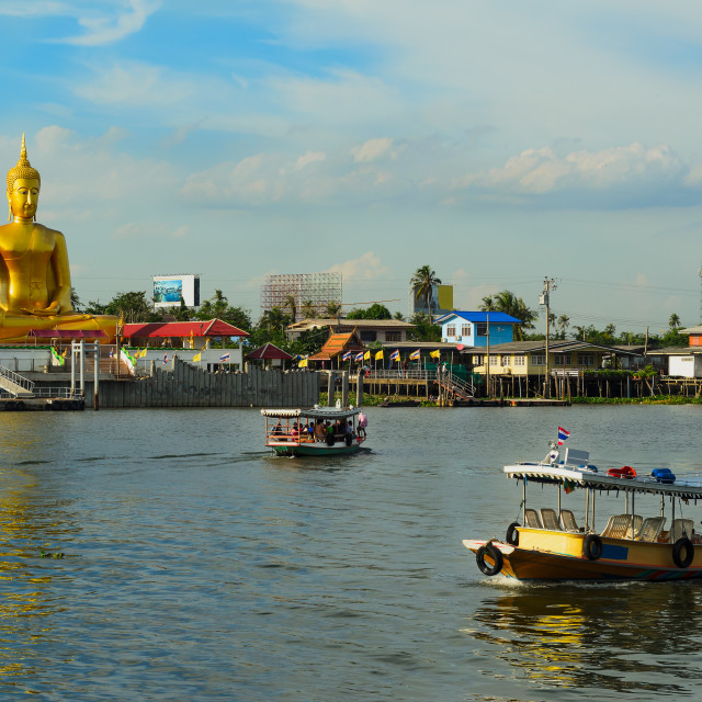 """River boats crossing the Chao Phraya river in Bangkok, Thailand,with a giant golden buddha and thai houses in the background"" stock image"