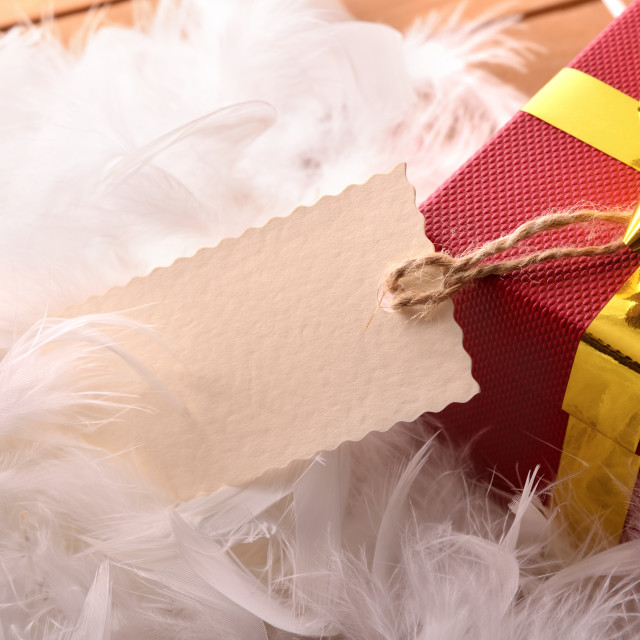 """Red gift box with tag hanging on feathers top wiew"" stock image"