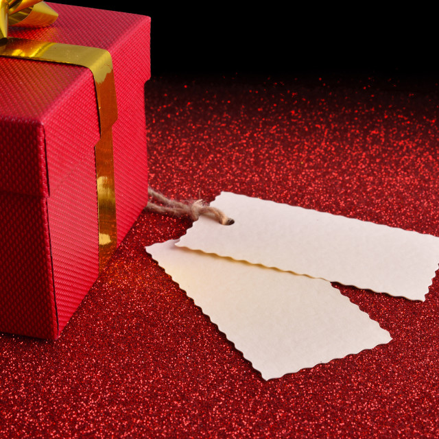 """Gift with two tags on bright red textured table elevated"" stock image"