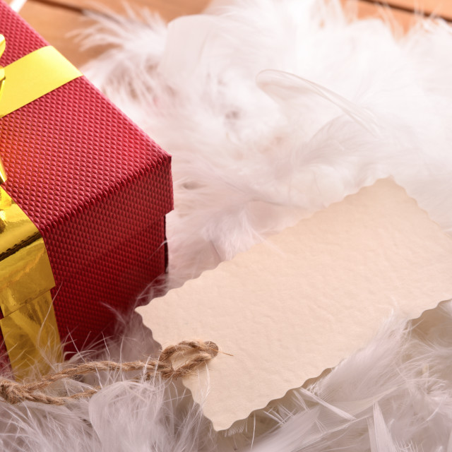 """""""Red gift box with tag on feathers top view"""" stock image"""