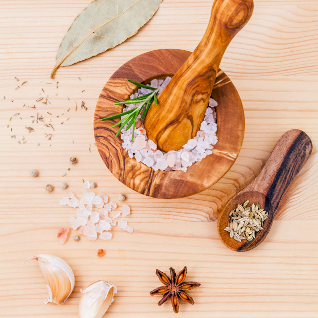 """Close up Himalayan pink salt in wooden mortar and herbs garlic ,dried thyme,..."" stock image"