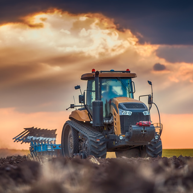 """Farmer in tractor preparing land with cultivator"" stock image"