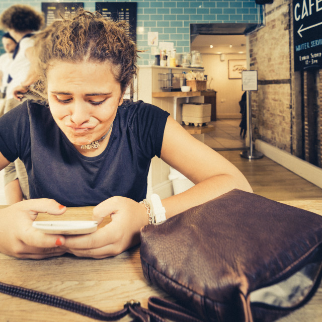 """""""Young woman watching her smartphone. Weird face"""" stock image"""