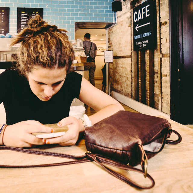 """""""Young woman texting in her phone in a cafe"""" stock image"""