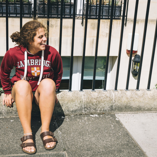 """""""Happy young student sitting in the street"""" stock image"""