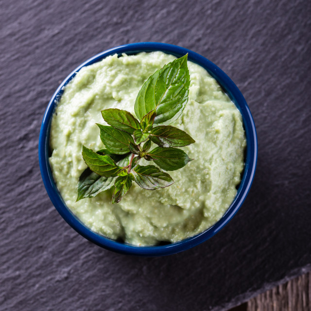 """Top view on bowl with wasabi dip with piece of herb"" stock image"