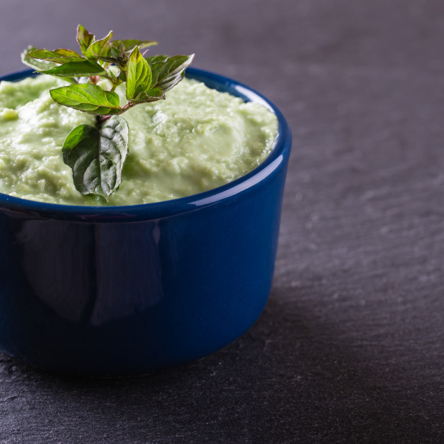 """Blue bowl with wasabi dip with piece of herb"" stock image"