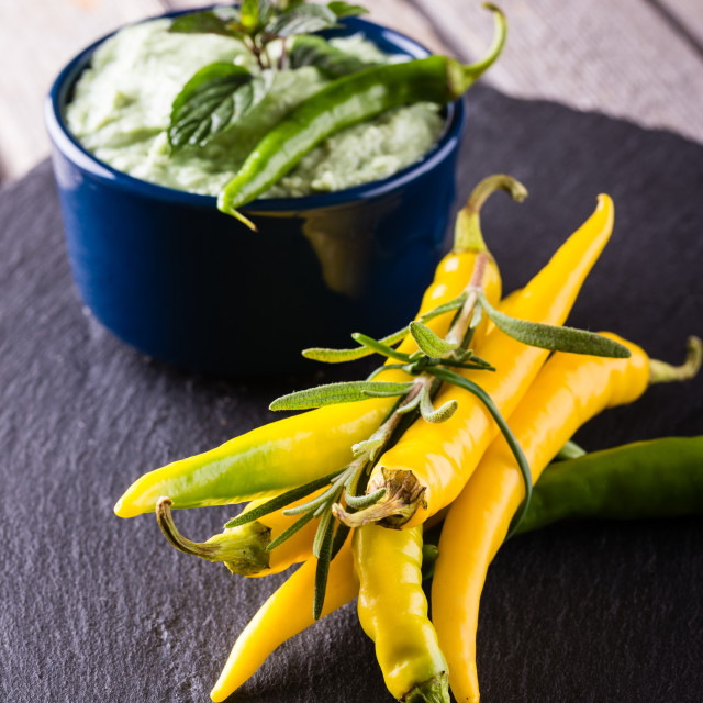 """Bunch of yellow and green chili pepers with wasabi dip in blue bowl"" stock image"