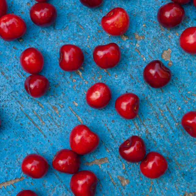 """Arrangement of ripe cherries on blue textrured background"" stock image"