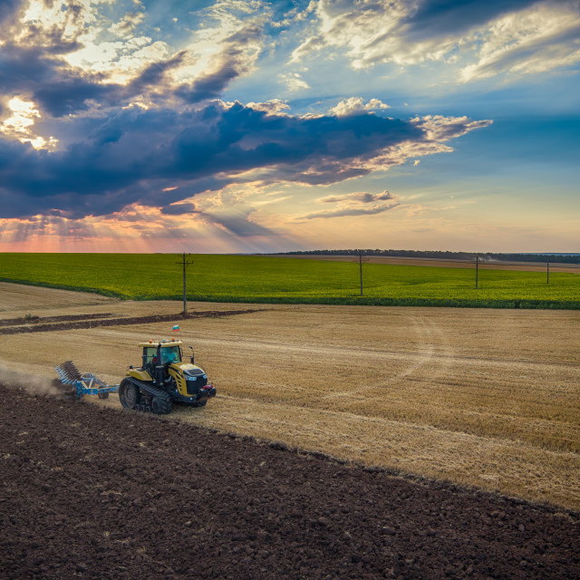 """""""Tractor cultivating field at autumn"""" stock image"""
