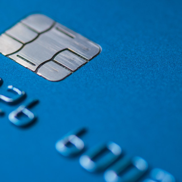 """Debit Credit card in blue with chip close up atm emv blurred, no labels and names. Macro detailed. Concept of personal finance, no cash payments."" stock image"