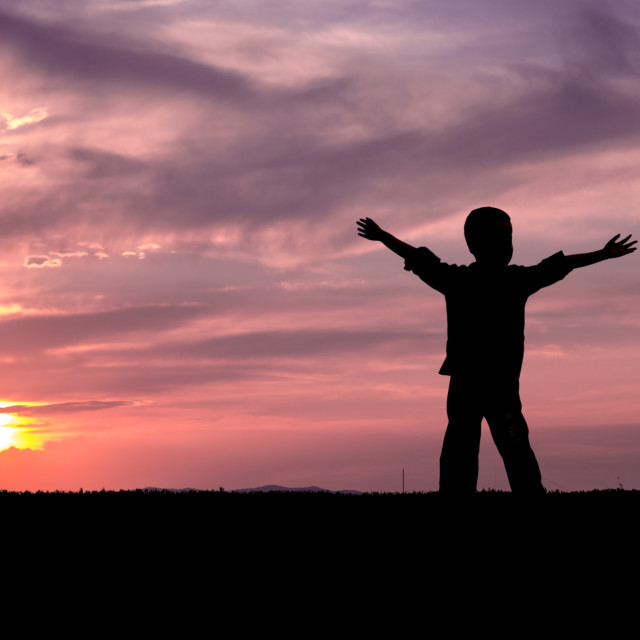 """""""Sunset child silhouette with raised hands looking into the sun and dramatic sky with clouds. Concept of happiness, freedom, youth, timeless, serenity, comfort, joy, childhood memories."""" stock image"""